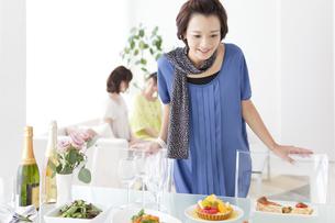 食卓に並ぶ料理を見ている笑顔の女性の写真素材 [FYI01289451]