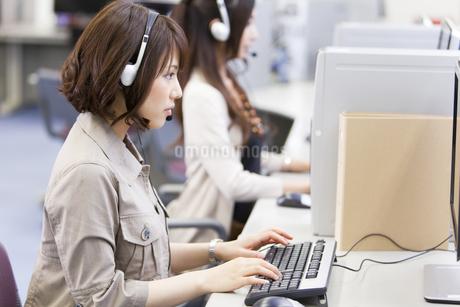 パソコンを操作するインカムを付けたビジネスウーマンの写真素材 [FYI01289455]
