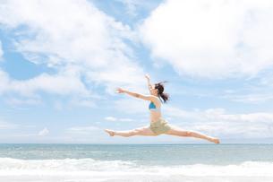 波打ち際でジャンプしている女性の写真素材 [FYI01289568]