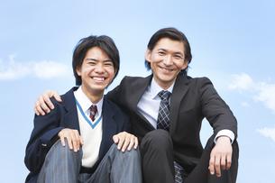 笑顔の男子中高生とスーツ姿の父親の写真素材 [FYI01289599]