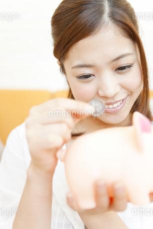 貯金箱にお金を入れる女性の写真素材 [FYI01289701]