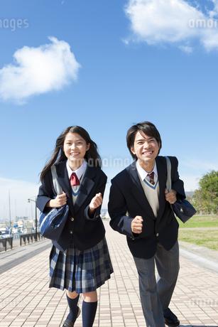 かばんを持って走り出す中高生の男女の写真素材 [FYI01289768]