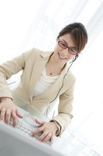 インカムを付けてパソコンを操作するビジネスウーマンの写真素材 [FYI01289809]