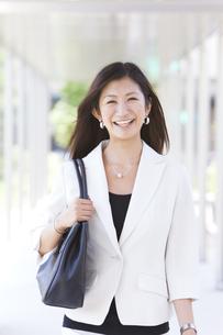 かばんを持っている笑顔のビジネスウーマンの写真素材 [FYI01289952]