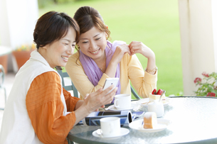 スマートフォンを見ている笑顔の女性2人の写真素材 [FYI01289958]