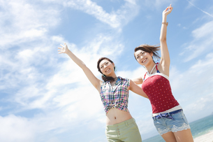 海辺で手を挙げている女性2人の写真素材 [FYI01290132]