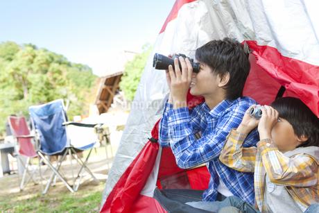 テントに入って双眼鏡を覗く親子の写真素材 [FYI01290521]