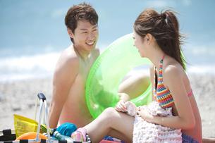 砂浜に座って会話する水着姿のカップルの写真素材 [FYI01290522]