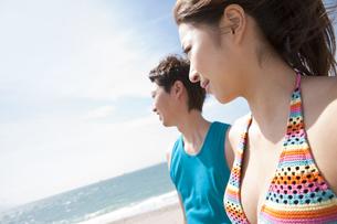 遠くを眺めている水着姿のカップルの写真素材 [FYI01290564]