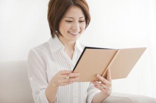 ソファーに座って本を読む若い女性の写真素材 [FYI01290571]