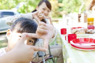 手でフレームを作る笑顔の親子の写真素材 [FYI01290572]