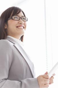 タブレットPCを持っている笑顔のビジネスウーマンの写真素材 [FYI01290682]