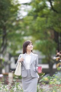 かばんとタンブラーを持って歩くビジネスウーマンの写真素材 [FYI01290739]