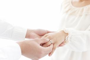 女性の指に指輪をはめる男性の手の写真素材 [FYI01290741]