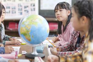 地球儀を囲んでディスカッションする小学生の写真素材 [FYI01290856]