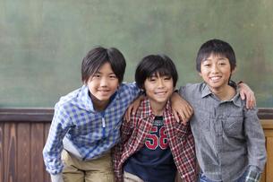教室で肩を組んでいる小学生の男の子3人の写真素材 [FYI01290857]