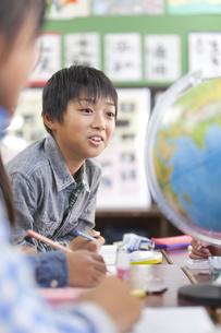 地球儀を囲んでディスカッションする小学生の写真素材 [FYI01290957]