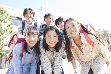 校庭に集まっている笑顔の小学生6人の写真素材 [FYI01290970]