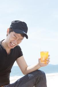 海辺でビールを飲んでいる男性の写真素材 [FYI01290988]