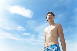 青空の下で遠くを見ている水着姿の男性の写真素材 [FYI01291016]