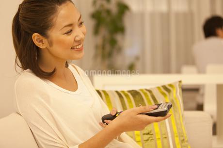 テレビのリモコンを持っている女性の写真素材 [FYI01291159]