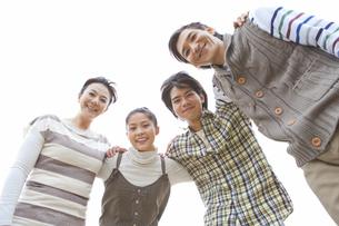 肩を組んでいる笑顔の家族4人の写真素材 [FYI01291321]