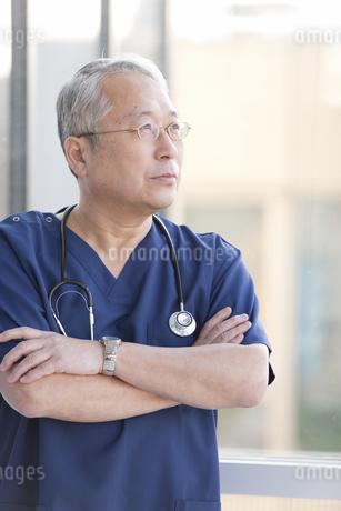 腕組みをして窓の外を見る医師の写真素材 [FYI01291387]