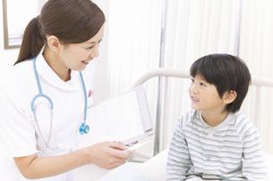 病室のベッドにいる男の子と看護師の写真素材 [FYI01291476]