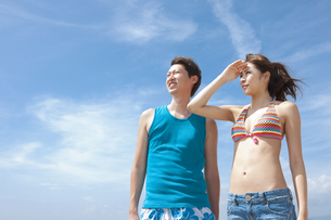 遠くを眺めている水着姿のカップルの写真素材 [FYI01291563]