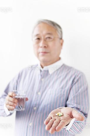 薬とグラスを手に持つシニア男性の写真素材 [FYI01291693]
