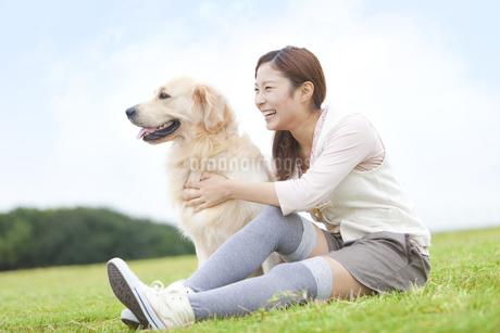 芝生に座っている女性と犬の写真素材 [FYI01291711]