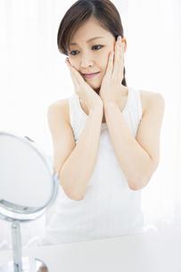 鏡を見ながらスキンケアをする女性の写真素材 [FYI01291741]