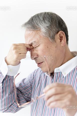 目頭を押さえるシニア男性の写真素材 [FYI01291772]