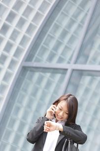 腕時計を見ながら通話するビジネスウーマンの写真素材 [FYI01292017]