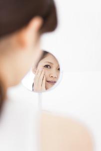 鏡を覗き込む女性の写真素材 [FYI01292026]