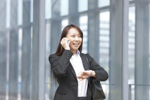 スマートフォンで会話をするビジネスウーマンの写真素材 [FYI01292027]