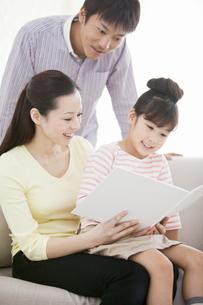 ソファで本を読む家族3人の写真素材 [FYI01292094]