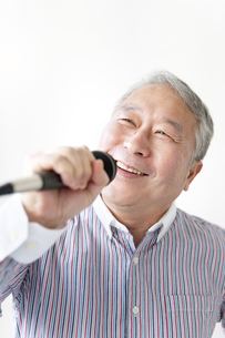 マイクを持って歌うシニア男性の写真素材 [FYI01292130]