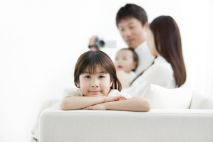 ソファに座る家族4人とビデオカメラの写真素材 [FYI01293131]