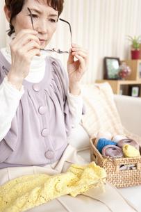 眼鏡をかけようとしている中高年女性の写真素材 [FYI01293206]