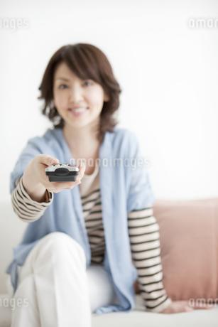 リモコンを持った女性の写真素材 [FYI01293434]