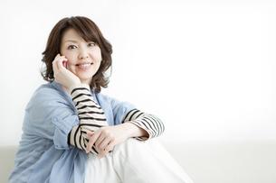 ソファーで電話をする女性の写真素材 [FYI01293448]