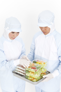 食品を調べている食品衛生服の2人の写真素材 [FYI01293739]
