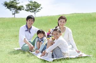 レジャーシートに座っている家族4人の写真素材 [FYI01293991]
