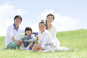 レジャーシートに座っている家族4人の写真素材 [FYI01294016]