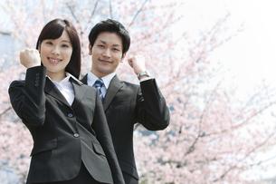 桜の前のビジネスマンとビジネスウーマンの写真素材 [FYI01294022]