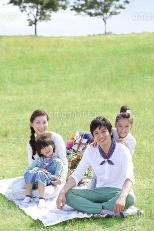 レジャーシートに座っている家族4人の写真素材 [FYI01294026]