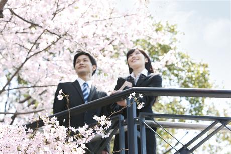 桜の前のビジネスマンとビジネスウーマンの写真素材 [FYI01294034]