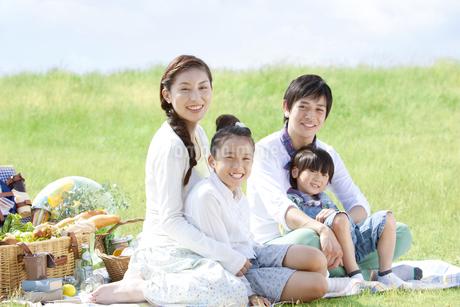 レジャーシートに座っている家族4人の写真素材 [FYI01294042]