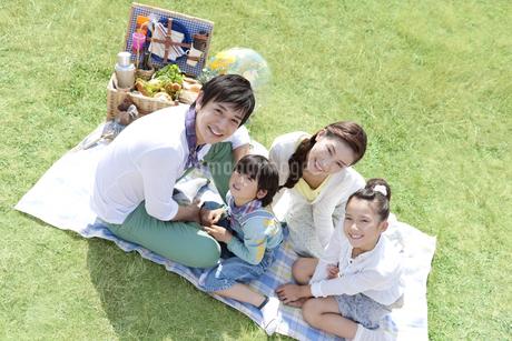 レジャーシートに座っている家族4人の写真素材 [FYI01294084]